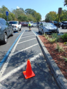 ADA Parking Survey in Florida. Inspecting the cross slopes of a shared accessible aisle of an accessible parking space. Disability Smart Solutions.